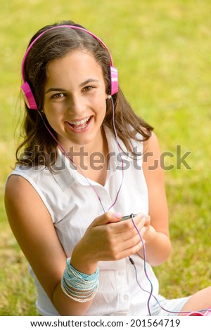 Laughing teenage girl listening to music sitting on grass summer - stock photo