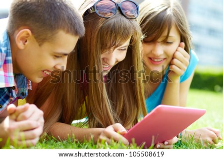 Laughing teenagers looking at the touchpad screen outdoors - stock photo