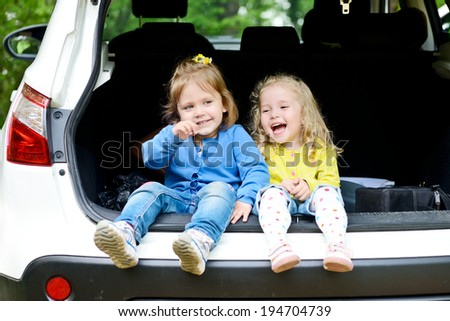 laughing toddler girls sitting in the car - stock photo