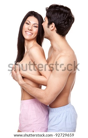 Laughing Topless Couple standing with their hands cupping the womans breasts, three quarter portrait on white - stock photo