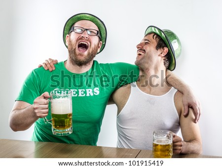Laughing uproariously, St. Patrick's Day friends at bar with large mugs of beer in matching green hats, mustaches, tank top, shirt, and glasses