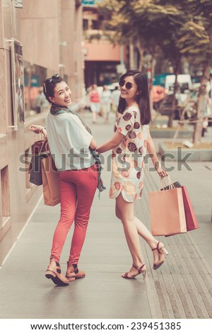 Laughing Vietnamese girls with shopping bags outdoors - stock photo