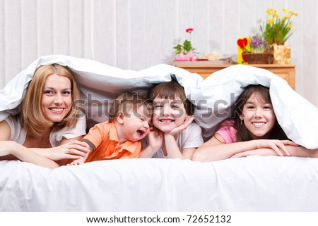 Laughing woman and kids covered with blanket - stock photo