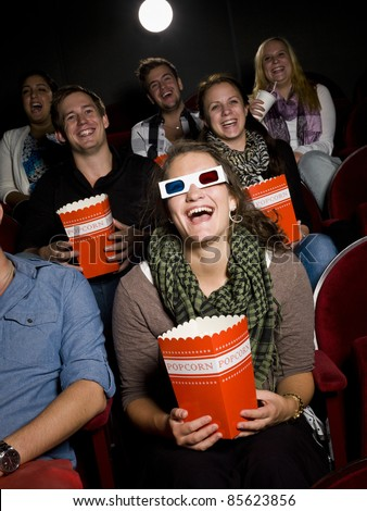 Laughing woman at the movie theater - stock photo