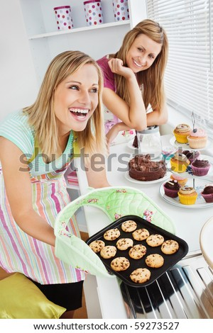 Laughing woman baking together in the kitchen - stock photo