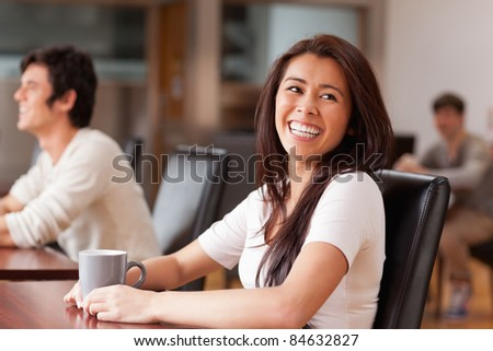 Laughing woman having a tea in a coffee shop - stock photo