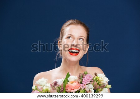 Laughing woman holding flowers and looking up over blue background - stock photo
