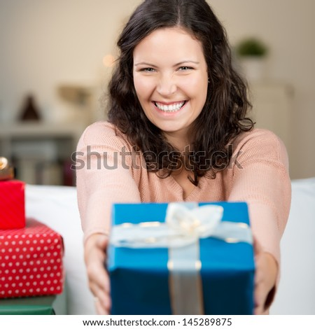 Laughing woman holding out a colourful gift at arms length offering it to the viewer with focus to her face - stock photo