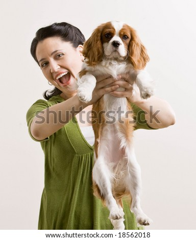 Laughing woman holding out pet dog - stock photo
