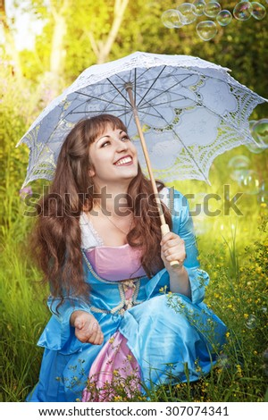 Laughing woman in medieval dress with umbrella and bubble blowers - stock photo