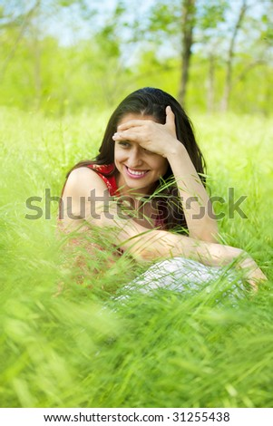 laughing woman sitting on green grass