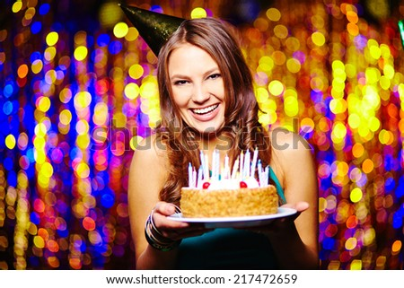 Laughing woman with birthday cake looking at camera - stock photo