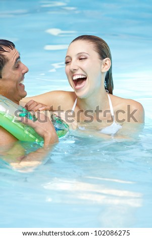 Laughing woman with happy man in floating ring in swimming pool - stock photo