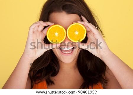 Laughing Woman With Orange Slices Over Eyes on orange studio backdrop - stock photo