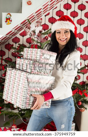 Laughing woman with santa hat holding stack of big Christmas presents