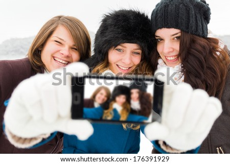 Laughing women taking photos with phone camera - winter selfie time. - stock photo