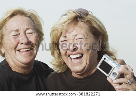 Laughing women with digital camera - stock photo