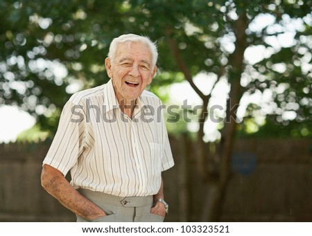 Laughing 90 year old senior man standing outside - stock photo