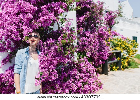 Laughing young blond woman wearing sunglasses and denim shirt with rolled up sleeves in sun surrounded by purple flower blooms on large shrub in garden - stock photo