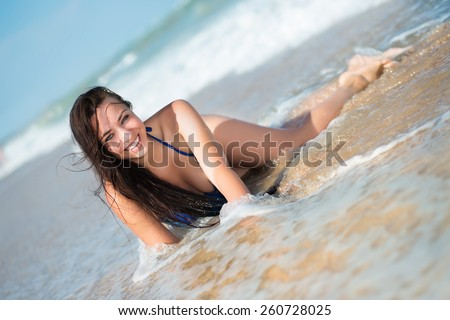 Laughing young brunette lying on the beach - stock photo