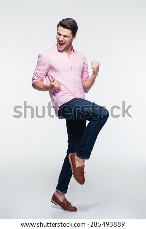Laughing young businessman celebrating his success over gray background. Looking away - stock photo