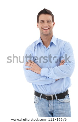 Laughing young businessman in casual clothing, standing with arms crossed, looking at camera. - stock photo