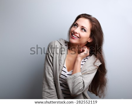 Laughing young casual woman looking up on blue background with empty copy space - stock photo