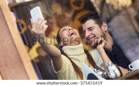 Laughing young couple making selfie in the cafe. - stock photo