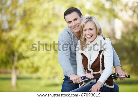 Laughing young couple on a bike outdoors - stock photo