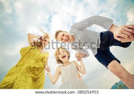 Laughing young family on the tropical sky background - stock photo