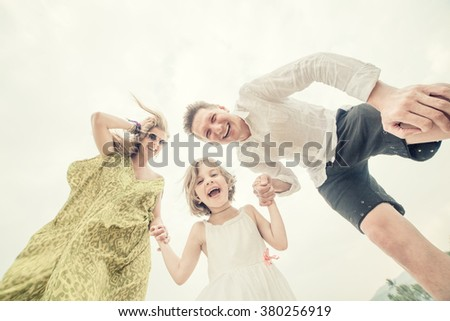 Laughing young family on the white sky background. Low contrast post-processing - stock photo