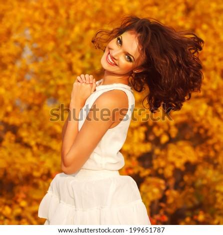 Laughing young girl in a white dress in the autumn park