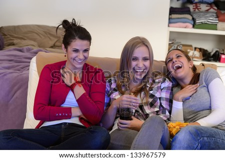 Laughing young girls watching TV together sitting on couch - stock photo