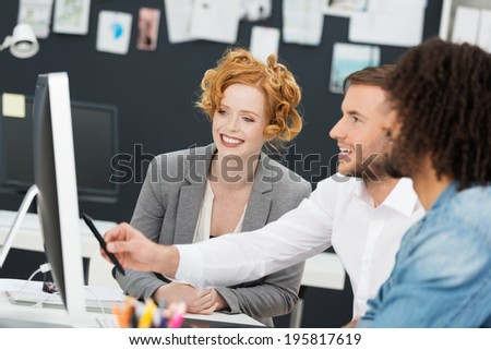 Laughing young group of businesspeople gathered around a computer monitor pointing and smiling - stock photo