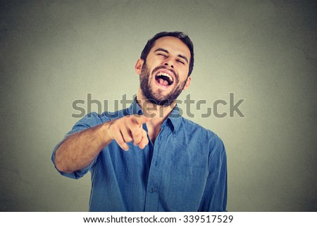 Laughing young guy pointing with finger at camera  - stock photo