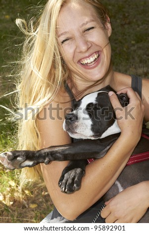 Laughing young lady embracing her sleeping Pit Bull puppy - stock photo