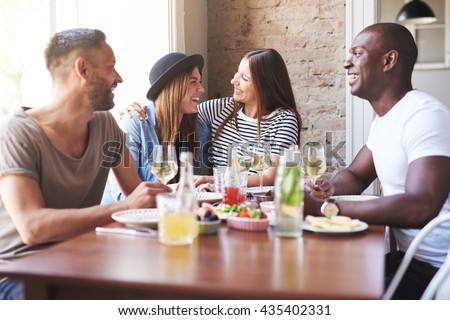 Laughing young men watching their girlfriends embrace each other at restaurant with large bright window and brick wall - stock photo