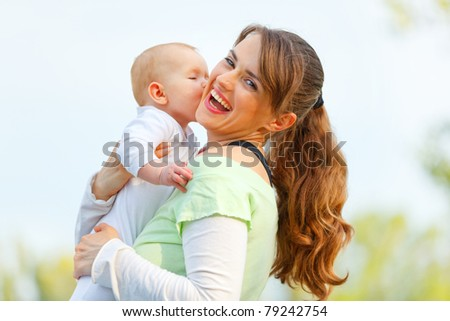 Laughing young mother hugging her baby in hands outdoors - stock photo