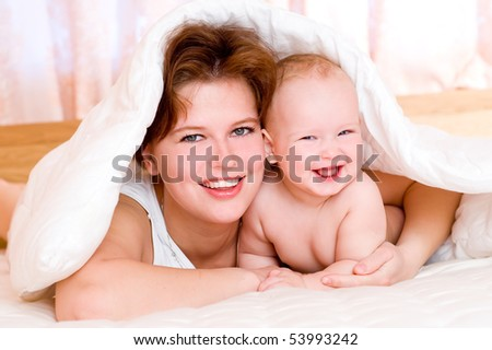 Laughing young mum and the kid under a white blanket