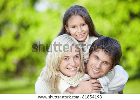 Laughing young parents with a daughter outdoors - stock photo