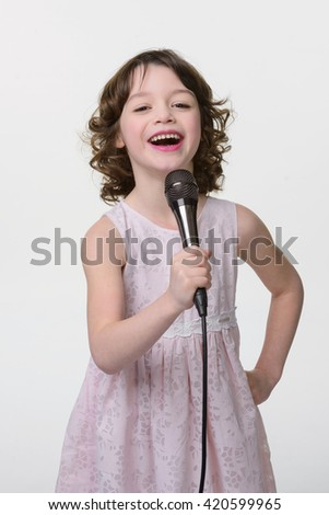 Laughing young singer stands with black microphone with cable in her hands. True positive emotions of joy and fun. Close-up portrait of caucasian female isolated. - stock photo