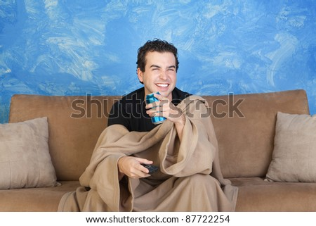 Laughing young with blanket on sofa with beverage can and remote control - stock photo
