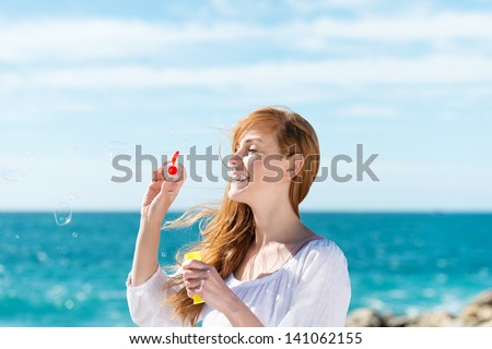 Laughing young woman blowing bubbles at the sea using a plastic ring and soap mixture - stock photo