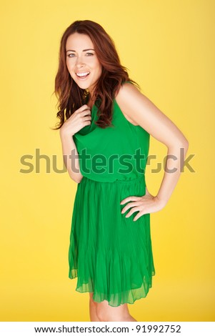 Laughing Young Woman wearing a green dress, three quarter on yellow studio background - stock photo