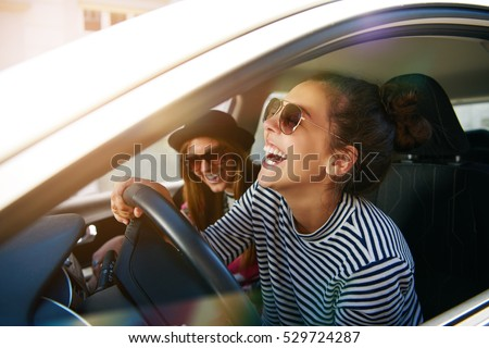Laughing Young Woman Wearing Sunglasses Driving Stock Photo