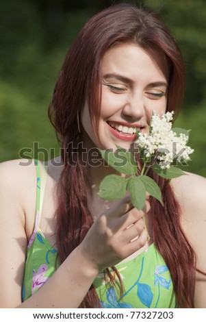 laughing young woman with flower in a park - stock photo