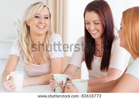 Laughing young Women sitting at a table with cups in a kitchen