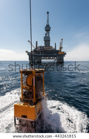 Launch remotely operated vehicle with a rig in background - stock photo