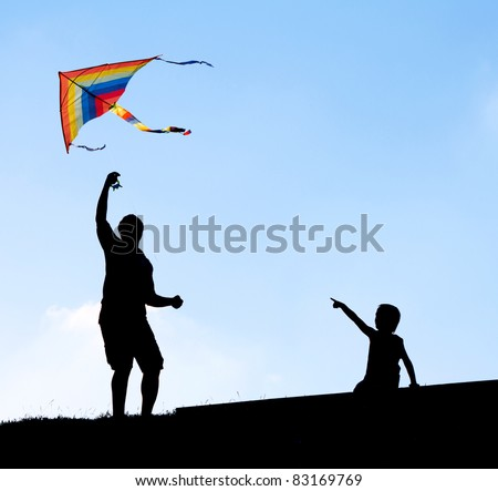 Launching a kite in the sky. Silhouettes man and children. - stock photo