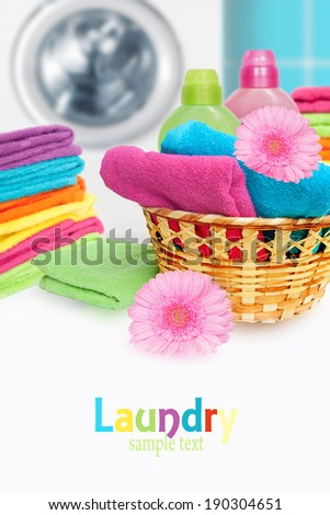 Laundry Basket with colorful towel and washing machine. - stock photo